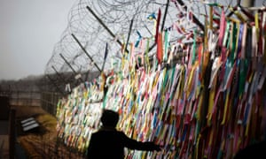 A tourist touches ribbons with messages wishing for reunification of the two Koreas on a barbed wire fence on the South Korean border with the North.