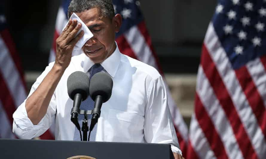 US President Barack Obama wipes sweat off his face as he unveils his plan on climate change June 25, 2013 at Georgetown University in Washington, DC. President Obama laid out his plan to diminish carbon pollution and prepare the country for the impacts of climate change.