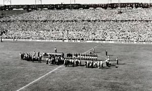 The teams line up at the start of the match as above the crowded stand a railway train passes.