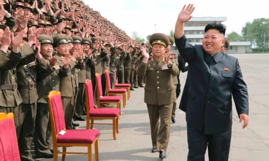 North Korean leader Kim Jong-un waves during a photo session with soldier-builders in this undated photo released by North Korea's Korean Central News Agency