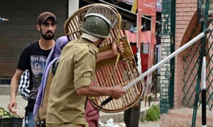 Kashmiri Muslims confront Indian policemen after they arrested a youth during a protest