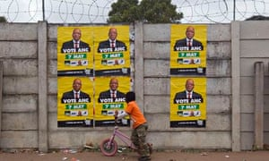 A boy walks past ANC election posters with images of Jacob Zuma in Embo, KwaZulu Natal