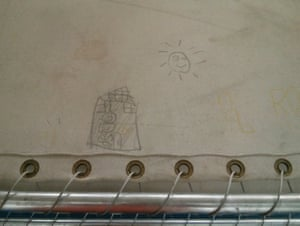 Children asylum seekers draw pictures on the canvas bunk beds