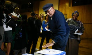 South African Nobel peace laureate Archbishop emeritus Desmond Tutu (C) and his wife Leah (R) cast their ballot in Cape Town on 7 May 2014.