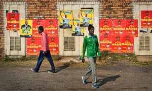 Two men walk past electoral campaign posters belonging to the African National Congress party and South African Communist Party in Soweto.