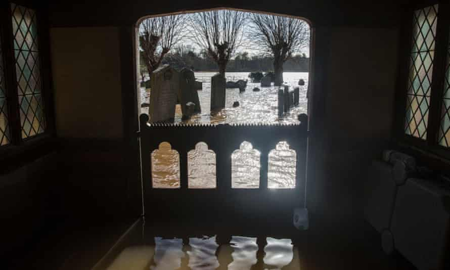 Gravestones surrounded by floodwater in the grounds of St Deny's Church in Severn Stoke, Worcestershire.