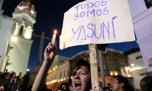 """A young man holding a sign that reads in Spanish; """"We are all Yasuni,"""" joins others in a candlelight vigil in front of the Ecuadorean government palace in protest against thre president's decision to allow oil drilling in the Amazon reserve, Yasuni National Park"""