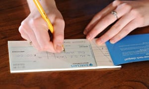 Young woman writing a cheque using chequebook UK. Image shot 2011. Exact date unknown.