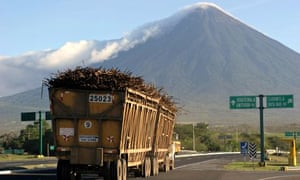 A truck loaded with cane drives to a sug