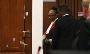 Judge Thokozile Masipa, to right of door in red cape, and her assessors examine the reconstructed toilet cubicle on Friday.
