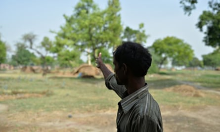 The father of one of the victims of gang-rape gestures towards the tree where his daughter was found