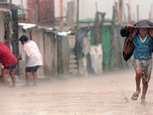"""Flooded dirt street in the town of Tuman, 820Km north of Lima, 17 March, 1998. Health authorities report that the flooding caused by the meteorological phenomenon """"El Nino"""" has exacerbated poor sanitary conditions in the poorest parts of Peru, provoking outbreaks of cholera, malaria, dysentery and conjunctivitis."""