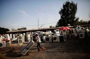 e-waste from the agencies: A recycling worker moves air-conditioning units