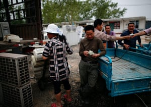 e-waste from the agencies: A man counts his money after selling recycled air-conditioning units