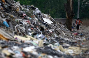 e-waste from the agencies: A woman walks near mounds of garbage