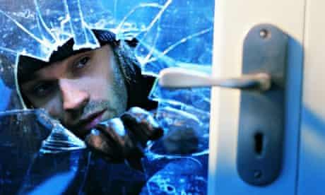 Burglar breaking through window