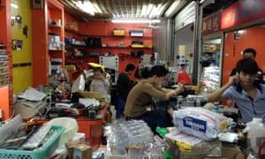 Family workshop inside a Huaqiangbei mobile phone market, Shenzhen, China.