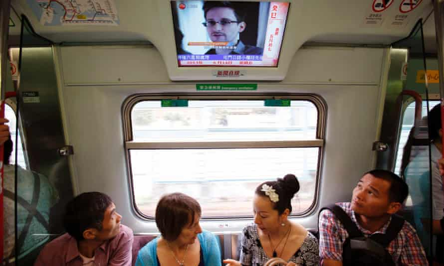 Passengers watch a television screen broadcasting news on Edward Snowden in Hong Kong.