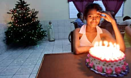 Wendy Aracely Hernandez, who has AIDS, looks at the candles on her birthday cake