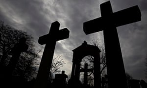Stone crosses and gravestones are silhouetted against the sky at Invaliden cemetery in Berlin