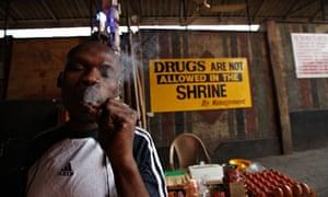 A man smoke Marijuana next to a no drugs sign in Lagos, Nigeria