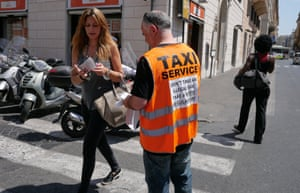 "An Italian taxi driver distributes leaflets reading ""Don't take an illegal taxi, take a white regular taxi"" during a protest against the growing number of minicabs and cars, known in Italy as Car rental with driver (NCC)."