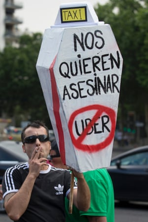 A demonstrator carries a mock coffin with a message reading 'They want to kill us - Uber' in Madrid, Spain,