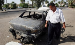 This 2007 photo shows an Iraqi traffic policeman inspects a car destroyed by a Blackwater security detail in al-Nisoor Square in Baghdad.
