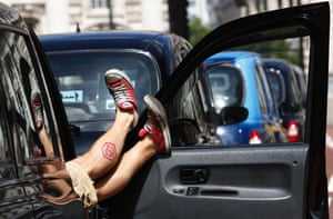 A taxi driver puts his feet up during a demonstration along the Mall in one of the biggest ever protests against Uber.