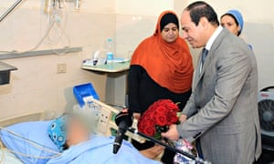 Egypt's President Sisi presents a bouquet of flowers to a woman at a hospital in Cairo