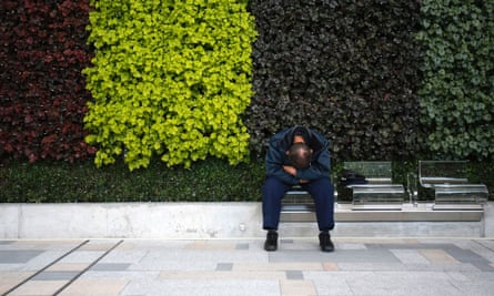 A man tries to take a nap at a bench in Tokyo, which has been designed to discourage sleeping.