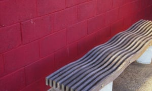 A wooden bench with a wavy seat to deter sleepers.