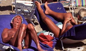 Snoozing sunbathers on loungers in Benidorm, Spain, with deep tans