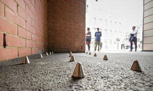 The inch-high conical spikes, with pedestrians in the background