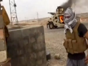 This video still shows a militant standing in front of a burning Iraqi Army Humvee in Tikrit, Iraq. The al-Qaida-inspired group that led the charge in capturing two key Sunni-dominated cities in Iraq this week has vowed to march on to Baghdad. Photograph: AP
