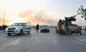 weds june 11 ISIL fighters stand guard at a seized checkpoint in the northern Iraq city of Mosul.