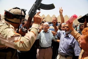 Iraqi men chant slogans against the al-Qaida breakaway group ISIL, outside of the main army recruiting centre to volunteer for military service in Baghdad after authorities urged Iraqis to help battle insurgents.