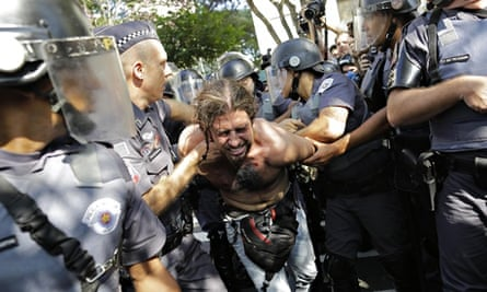 A man is detained by police in a protest over the cost of the World Cup near the Arena Corinthians
