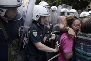 Cleaners laid-off by the Finance ministry are pushed back by riot police in their attempt to protest outside the ministry in Athens on June 12, 2014
