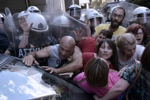 Cleaners laid-off by the Finance ministry are pushed back by riot police in their attempt to protest outside the ministry in Athens on June 12, 2014.