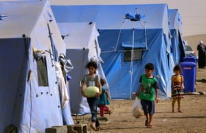 Children walk outside temporary tents set up to shelter Iraqis fleeing violence in Iraq's northern Nineveh province in Aski Kalak, 40 kms West of Arbil, in the autonomous Kurdistan region.