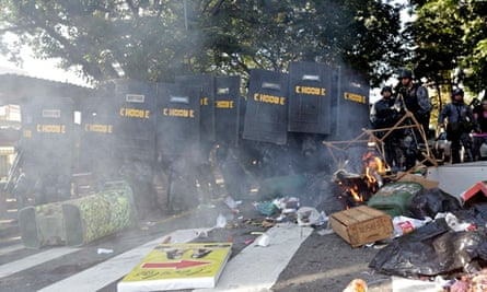 Riot policemen hide behind shields during a protest against the 2014 World Cup in Sao Paulo