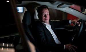 Elon Musk in a Tesla car.