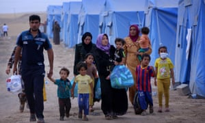 An Iraqi family walks past tents at a temporary camp set up to shelter Iraqis fleeing violence in Iraq's northern Nineveh province on June 12, 2014, in Aski kalak, 40 kms West of Arbil, in the autonomous Kurdistan region.
