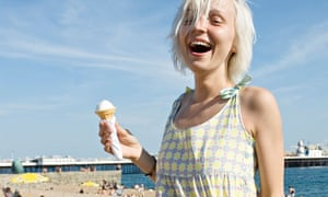 A young woman holding an ice cream cone at the beach - cycling guide page 90