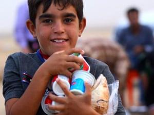 An Iraqi refugee boy carries food at a refugee camp near the city of Erbil, northern Iraq.