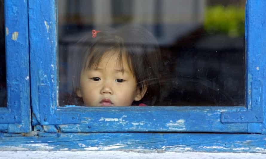 In this photo released by the World Food Program a North Korean child peers through a window at a creche in Hyangsan, in North Korea, in 2006.