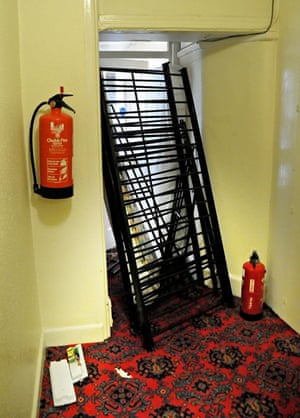 A fire door blocked by beds and mattresses.