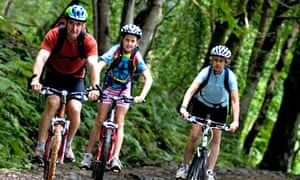 Group of three cyclists in Grizedale Forest Lake District UK