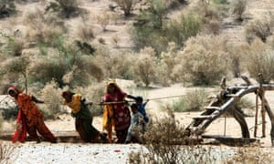 Women struggle to get water from a well in famine-hit Deeplo, Sindh province, Pakistan, March 2014.